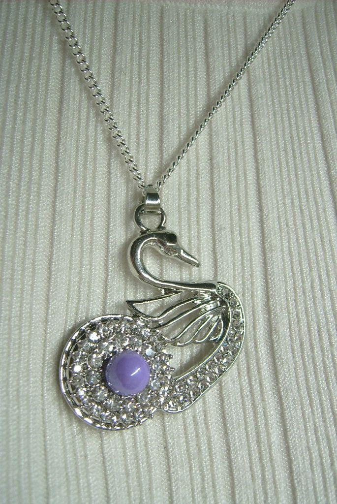 Kristály színű köves, valamint lila gyöngyös, fém, hattyú medálos nyaklánc. A nyaklánc hossza: 41 cm. A medál mérete: 45 x 36 mm. 590.-Ft.