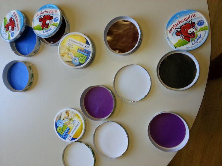 Kaasdozen bekleven met gekleurde cirkels.  De kleuters zoeken de dozen met de identieke cirkels.