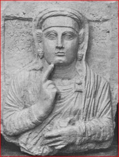 Tamma was buried between 100-120 CE.  She was the only woman in Sassans tomb whose father and mother were both named on her funerary stone. She touches her chin with her right index finger. Her other hand holds spindle and distaff. She wears a broad, rather plain headband and a twisted turban below a veil.  Her ornaments are a brooch  and bunch-of-grapes earrings.