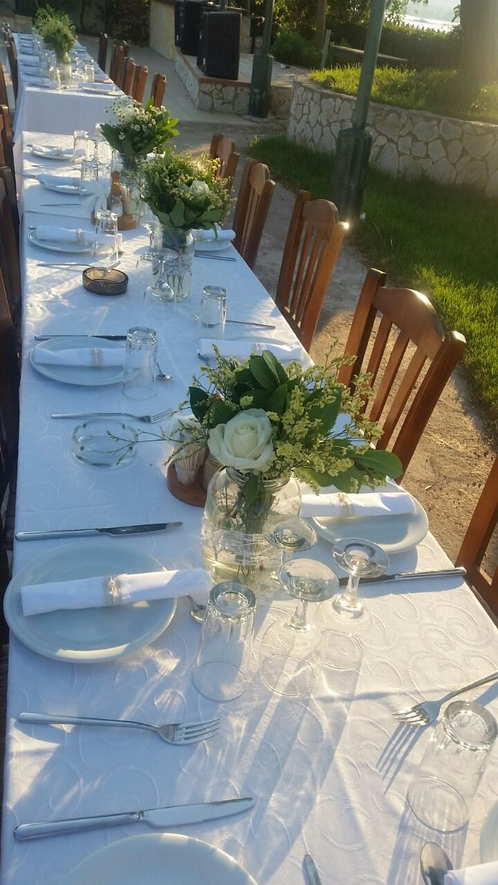 Wildflower wedding table vases decoration with white roses and eucalyptus at traditional Greek wedding by Gourioti Flowers