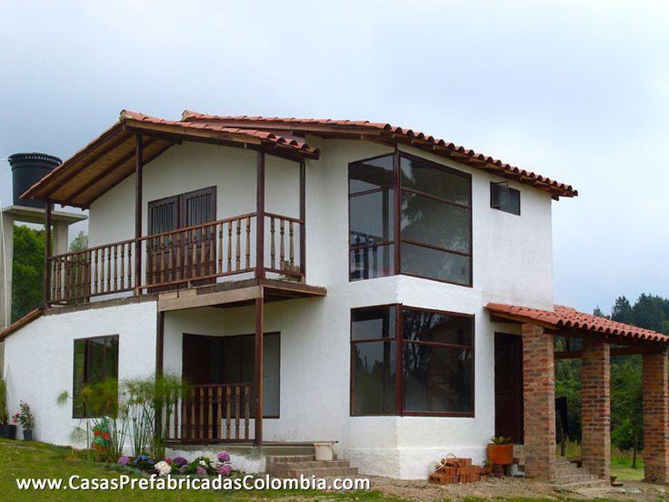 Casa de dos niveles en teja de barro, puertas y ventanas metálicas, balcón, barandas en madera.