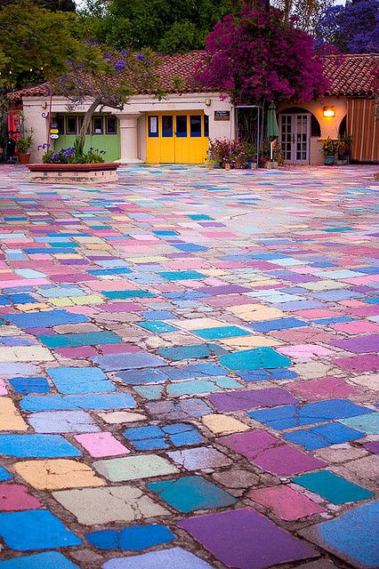 Love the colorful driveway...wonder if chalk or paint was used. If it was chalk, I'd imagine it would be messy and washed away far too easily...maybe paint that has a chalk-looking texture to it.