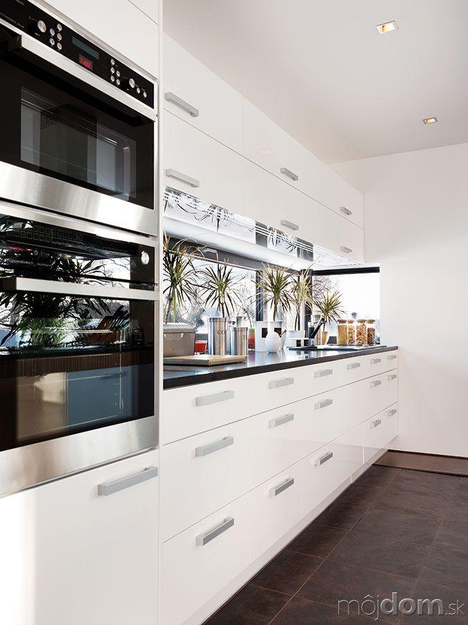 Pracovnú plochu vkuchyni efektne osvetľuje úzke pásové okno. Kombinácia bielych atmavých plôch osvetlených prirodzeným svetlom pôsobí elegantne azároveň príjemne.