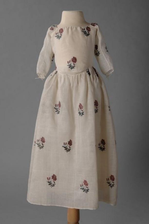 1750-1785, Kinderjurk van ecrukleurige mousseline en met veelkleurige getamboereerde zijden bloemen, rijgsluiting achter, vierkante hals en driekwart mouwen | Modemuze