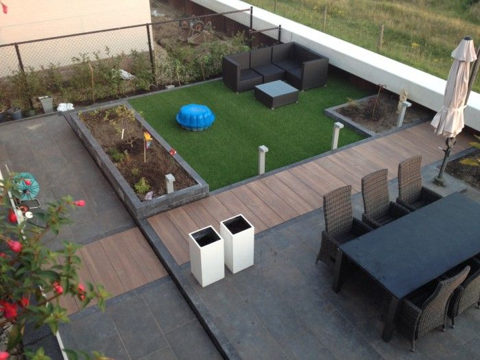 mooi terras met keramische terrastegels in hout look 30x120x2 cm en antraciet roestkleur 45x90x2 cm. Hardsteen stapelblokken gezoet 12x12x50 cm in de verhogingen en borderbakken.