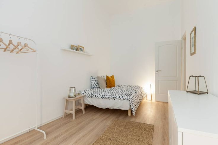 Wooden floor, white walls and light-colored bed linen.