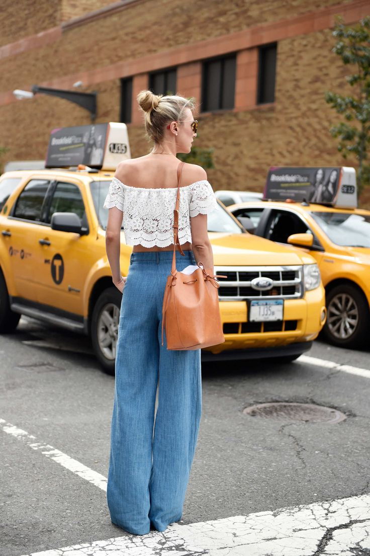 Wide leg jeans with an off the shoulder lace top and bucket bag.