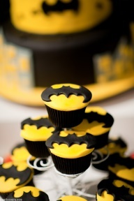 batman birthday cupcakes.   aka. my next birthday cupcakes.   just use icing that is thinker/harder.   roll out the icing and cut out yellow circles with a cookie cutter.   use a precision knife for batman symbols.