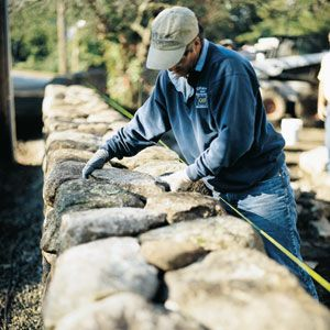 A stone wall along the property line is one way to lessen traffic noise. Here, a mason works to complete a 2½-foot-tall one at TOH TV's Carlisle house. Even a low wall affects noise coming from tires on the road.