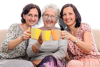 Senior lady and two adult women holding a cup of hot wine drink to that. Family having fun holding colored cups at home on the sofa, isolated on white.