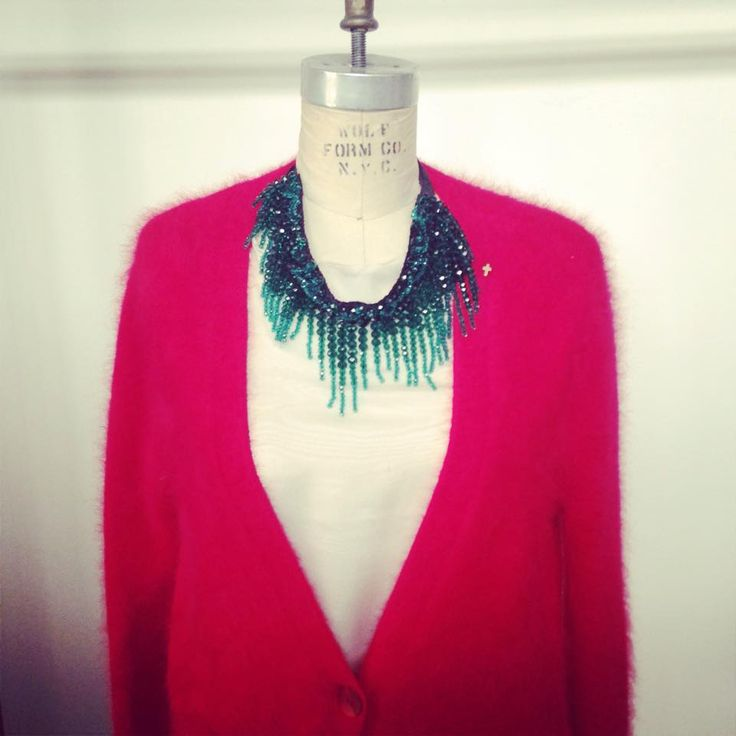 Red knitwear and emerald necklace
