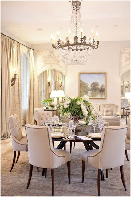 A very elegant dining room with a nice sitting area in the back.