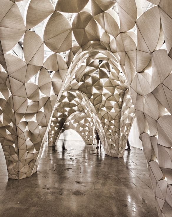 'Voussoir Cloud', a site-specific installation by San Francisco based architecture and design practice IwamotoScott in collaboration with Buro Happold. a system of three-dimensional modules formed by folding paper thin wood laminate along curved seams.