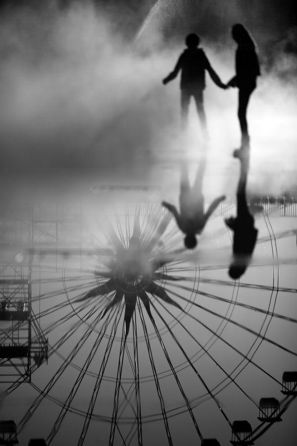 La coulée verte à #Nice. Des enfants pataugent dans la flaque formée par les jets d'eau avec le reflet de la roue de la fête foraine. Photo d'art noir et blanc                                                                                                                                                      Plus