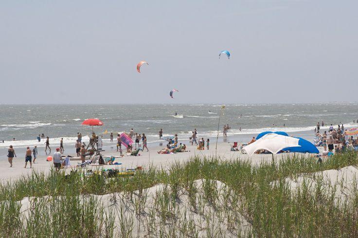 Sunbathers watch as windsurfers chase the waves at Folly Beach County Park, South Carolina.