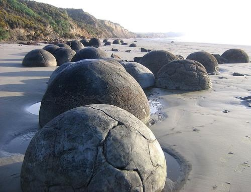 The Moeraki Boulders, Newzealand - cattered along the beach at Moeraki which is some 40 kilometers south of Oamaru, the boulders are a popular visitor attraction. The soft mudstone containing the boulders was raised from the sea bed around 15 million years ago and sea erosion of the cliff is exposing the erosion-resistant boulders.