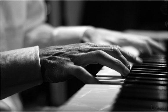 wrinkled hands on ivory keys...