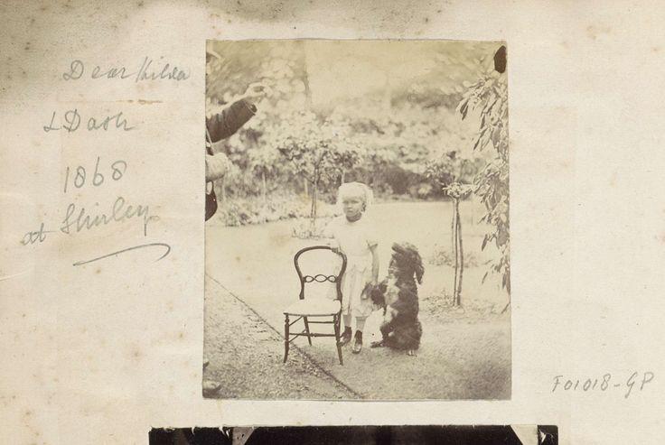 Anonymous | Klein meisje en een hond poserend bij een stoel buiten, Anonymous, 1868 | Onderdeel van Engels familiealbum met foto's van personen, reizen, cricket en kunstwerken.