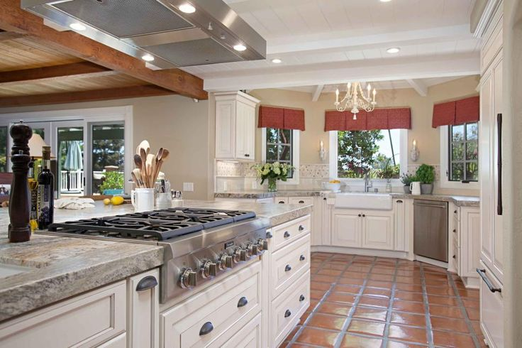 Beautiful white cabinets pair with warm terra cotta tile floors in this French country-inspired kitchen. A cooktop is incorporated into the large island, which provides ample storage space.