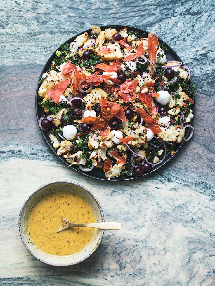 { Ingredienser til 2 personer som hovedmåltid / 4 personer som tilbehør } 1 blomkål Salt 1 spsk. olivenolie 2 dl quinoa (gerne sort) 1 tsk. salt eller 1 boullionterning 6 dl vand 100 gram grønkål, stik fjernet 75 g serranoskinke 1 lille rødløg 1 håndfuld røde vindruer 125-150 g mozzarella (gerne minikugler) { Honning-sennepsdressing } 3 spsk. mayonnaise 1 spsk. honning 1 spsk. dijonsennep Salt og friskkværnet peber Tænd ovnen på 175 grader. Rengør blomkålen, og skær hovedet ud i buketter og…