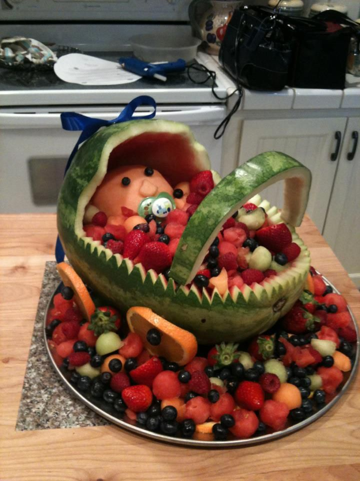 Baby carriage fruit basket for baby shower. Cut watermelon and shape with paring knife. Baby head is half of a canteloupe, peeled.