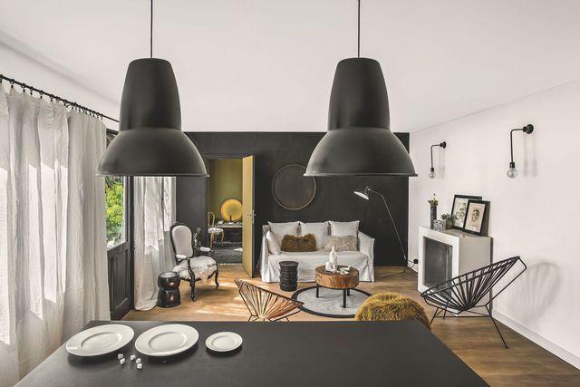 Un beau salon filtré par des rideaux en étamine de lin et une touche noire chic