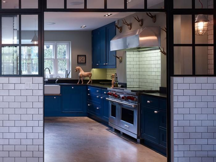 Blue cabinet faces add color to an otherwise neutral palette. The cabinets were custom designed by Stiff   Trevillion.