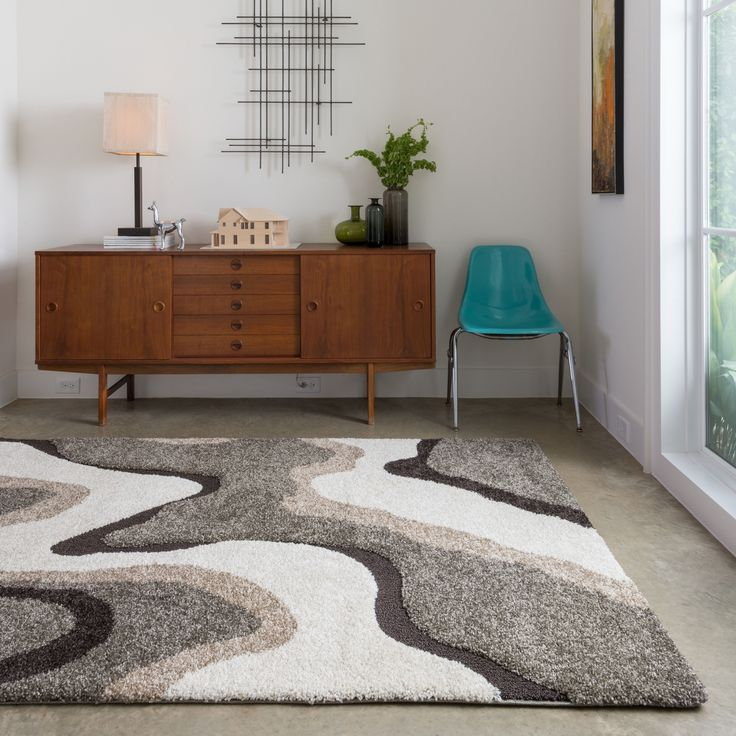 Add bold styling underfoot with this thick shag rug that features an abstract design in colors of gray, brown, and ivory. This large rug is an inch thick to add fantastic warmth to cold toes and chilly floors. Pop it somewhere you like to relax.