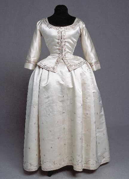 Gown, 1770-1780, Sweden, silk. Consisting of jacket and skirt. White atlas silk with small scattered flowers embroidered to skirt in stem stitch with silk in bright colors of green and red. Jacket is fully lined with linen, round neckline, three quarter long straight sleeves. The jacket has front closing lacing and a hook and eye closure at the waist with two pairs of hooks and eyes. ©2013 Kulturen i Lund