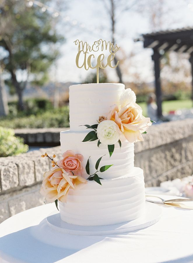 Three tier rose and ranunculus topped wedding cake: http://www.stylemepretty.com/california-weddings/fallbrook/2017/02/17/peach-spring-outdoor-wedding/ Photography: Sara Weir - https://www.saraweirphoto.com/