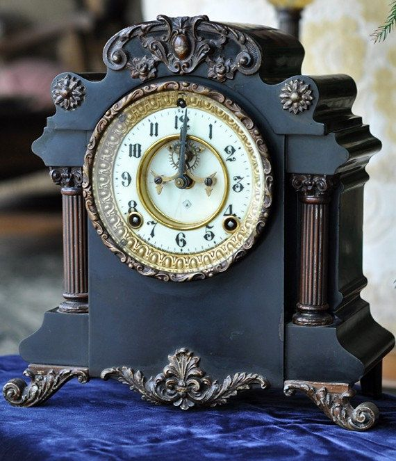 """An Ansonia """"Munich"""" mantle clock with a porcelain dial and visible escapement. A black clock with metal elements that have a nice patina. This should look good just about anywhere."""
