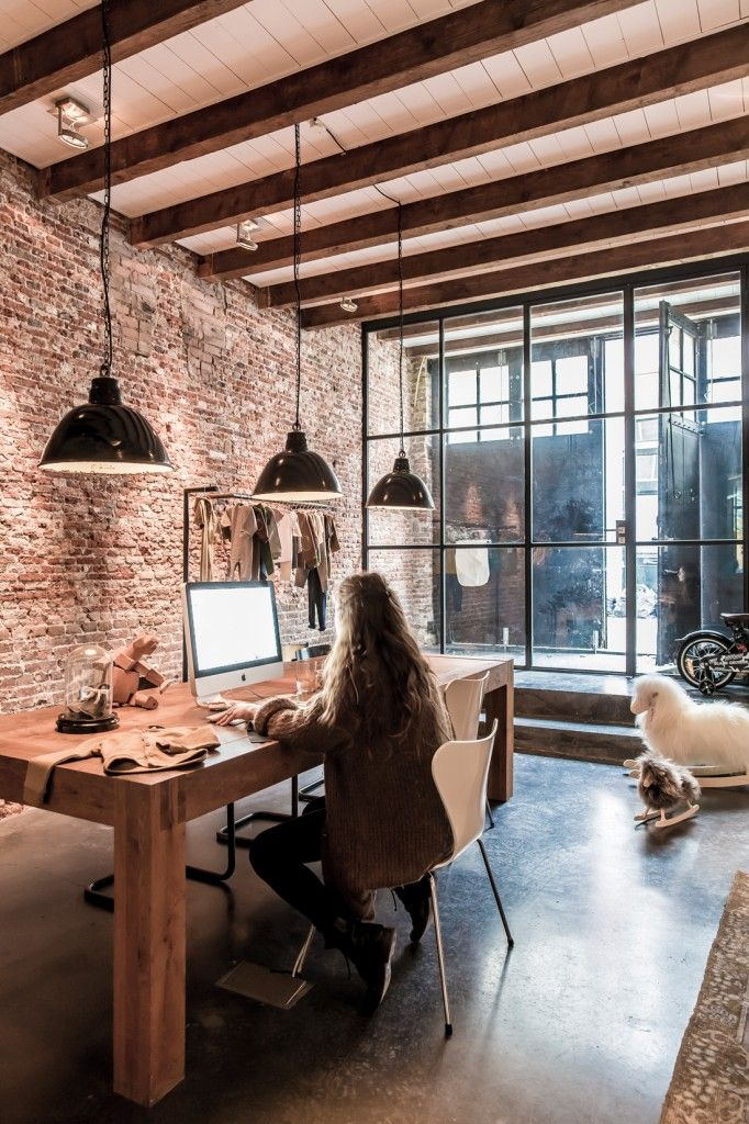 This chunky table paired with a textured exposed brick wall and large paned glass windows... such a great space!