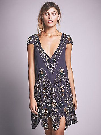 Magic Garden Party Dress   Trapeze-cut mini dress with cap sleeves, V-neckline, and a beautifully sculpted hem. Intricately embellished with vintage-inspired beadwork and sequin design. Sheer dress, with slip included.