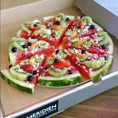 Een leuke traktatie: Fruitpizza met een bodem van meloen en een topping van andere stukken fruit.