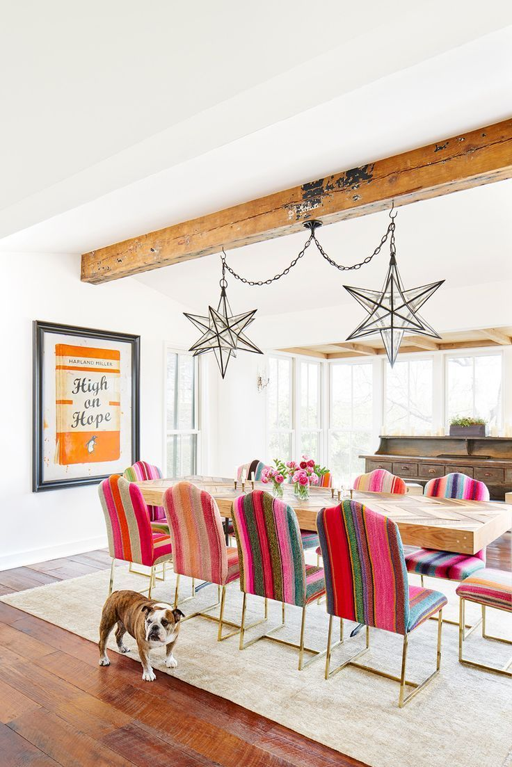 Modern southwestern style in a dining room design featuring chairs upholstered with colorful serapes, a herringbone wood table top, rustic wood sideboard, exposed wood beams, and Moravian star pendant lights - Dining Room Decor & decorating Ideas - mydomaine.com
