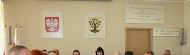 Herb Gminy i godło RP w sali posiedzeń Rady Gminy. Haft jest atrakcyjniejszy i bardziej prestiżowy od herbów drukowanych.