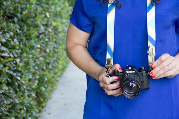 Use painter's tape and paint to add blocks of color to a canvas camera strap.