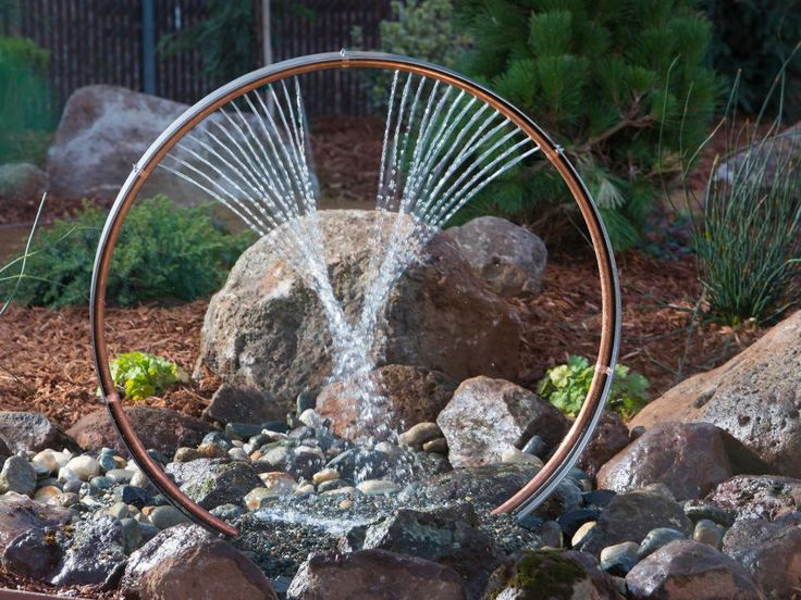 In the custom designed water feature, water sprays in a crisscross pattern and flows into the rocks below.