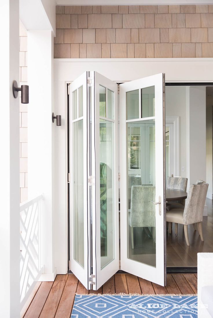 It's Memorial Day weekend! Go outside and play in the beautiful sunshine. This tri-fold door that leads from the breakfast nook to the great outdoors encapsulates freedom and Summer for us! | Coastal Contemporary designed by Alice Lane | Photographed by Lindsey Gerulat https://alicelanehome.com/portfolio/coastal-contemporary/