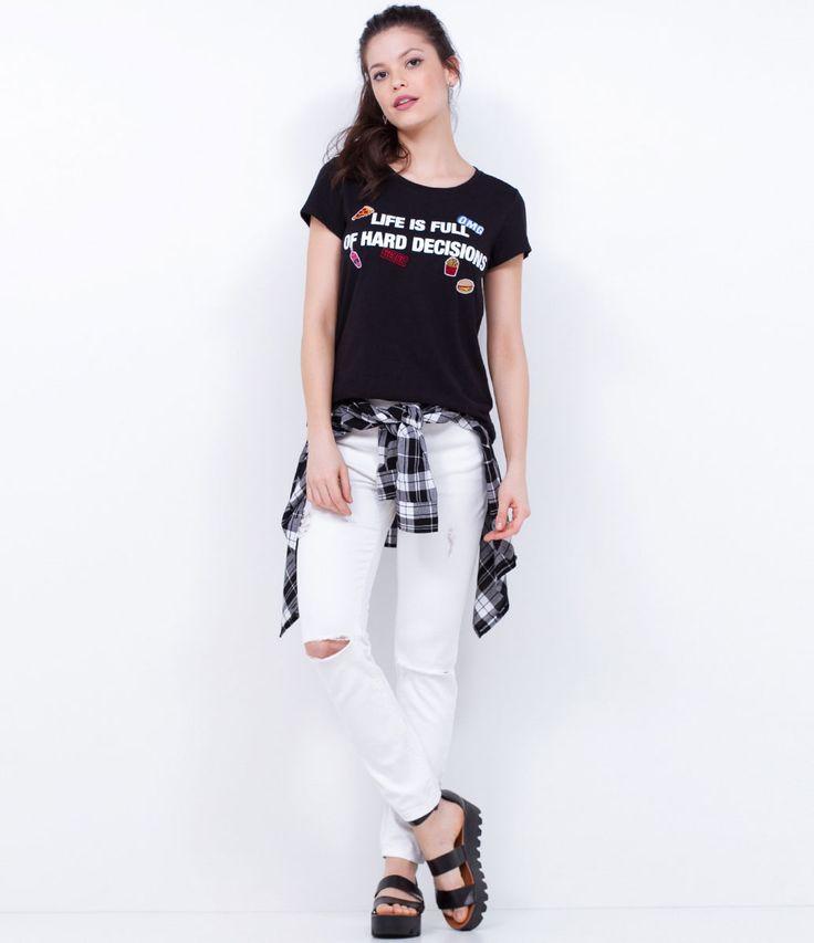 Look com camiseta de frase com patches, calça branca e sandália flatform.