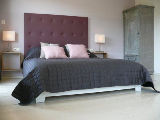 Slaapkamer met bed met paars hoofdeinde en vierkante 'nachtkastjes'