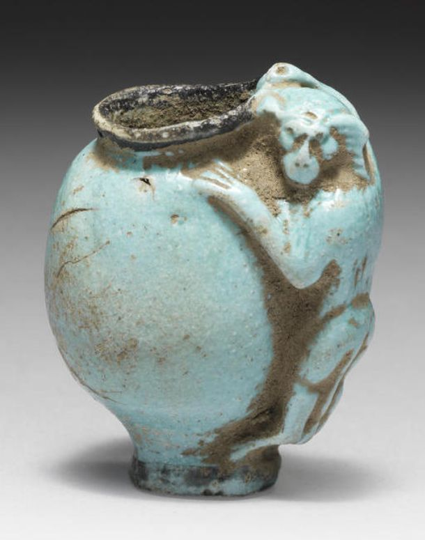 Egyptian turquoise glazed composition cosmetic pot:  New Kingdom - Third Intermediate Period, 1550-702 B.C. The body is egg-shaped, w/small low foot & black-rimmed neck, the handle is in the form of a standing monkey,  1½in high