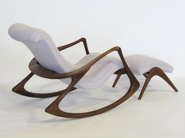 Contour rocking chair by Vladimir Kagan has a smooth wooden frame and white molded seat and ottoman.