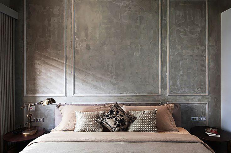 A boiserie e o cimento queimado na parede compensam a falta de cabeceira e dão um ar retrô desgastado ao quarto.