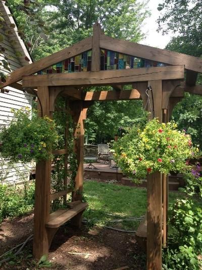 Rustic arbor made of timbers - love the stained glass insert at the top.