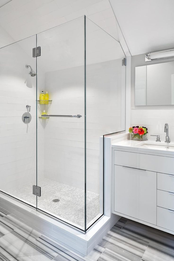 White, modern cabinetry, crisp white tile and sleek gray accents turn this small bathroom into a modern haven. A frameless glass shower enclosure opens up the small space and fits well with the room's streamlined design. The floating vanity's vertical lines are echoed in the lighting and tile.