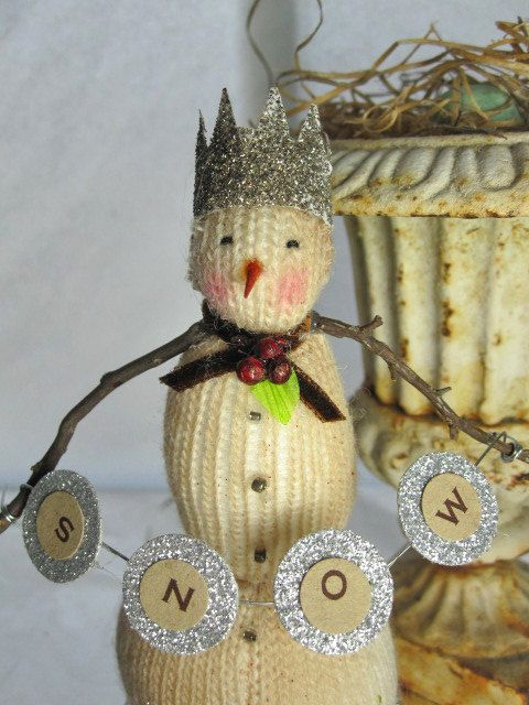 This darling snowman is a tiny charmer. He is made from tea dyed knit fabric. Atop his heads sits a silvery glittered crown. At his neck is a brown