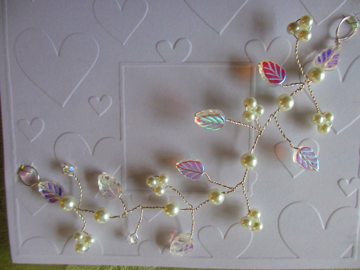 Hand wrapped wire hair vine. Crystal pearls and crystal iridescent leaves. 6'' long with hair pins  $30.00