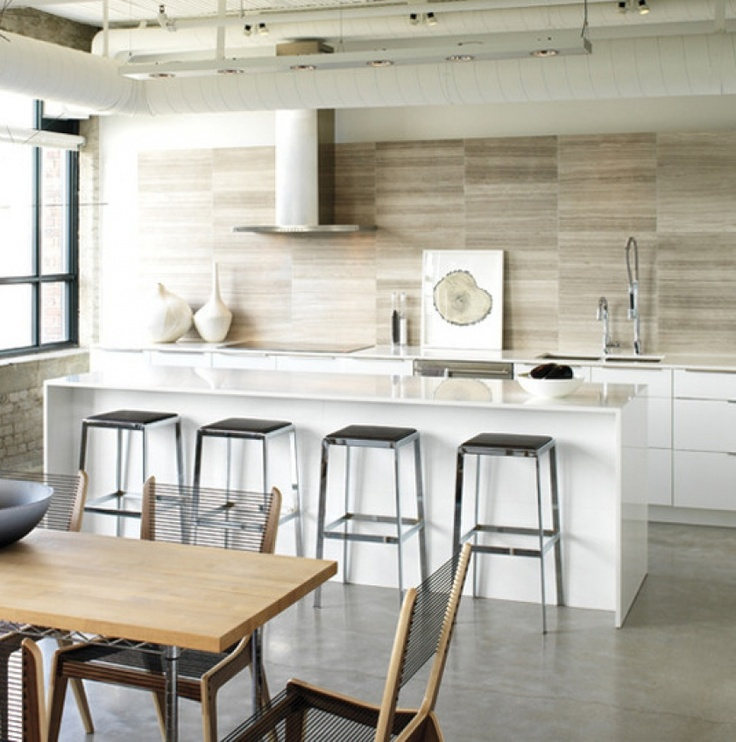 Designers Amy Kent and Ryan Martin of Croma Design added a custom touch to a glossy white IKEA kitchen with a CaesarStone counter and travertine tile backsplash. It's a focal point and backdrop for art like Adrienne Veninger's Tree Circle. Forgoing upper cabinets lends sleek sophistication.