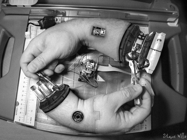 This is 'Hand Fixing Hand', a transhumanist version of M.C. Escher's 'Drawing Hands' (links to original) by Shane Willis.